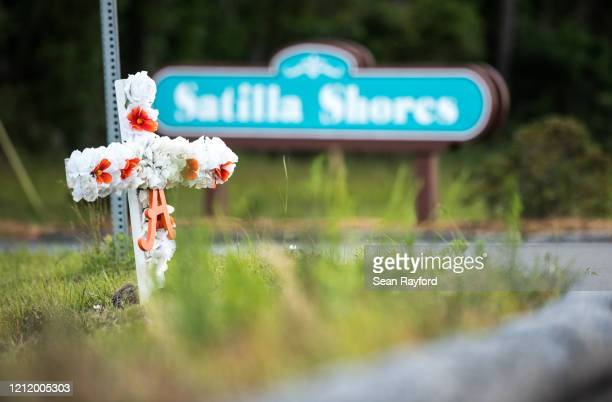 A cross with flowers and a letter A sits at the entrance to the Satilla Shores neighborhood where Ahmaud Arbery was shot and killed on May 6 2020 in...