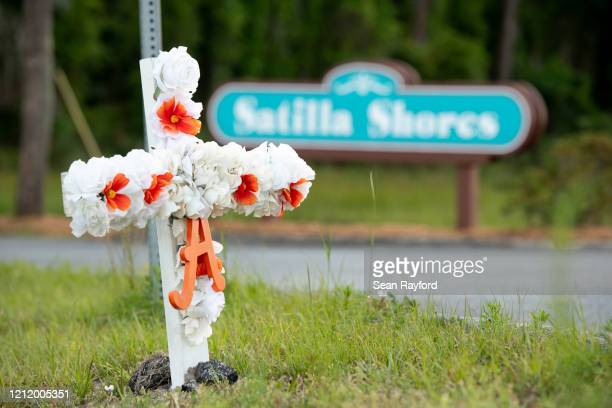 "Cross with flowers and a letter ""A"" sits at the entrance to the Satilla Shores neighborhood where Ahmaud Arbery was shot and killed on May 6, 2020 in..."