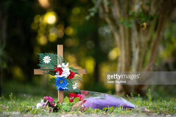Cross with flowers sits near the intersection of Satilla Rd. And Holmes Rd. In the Satilla Shores neighborhood where Ahmaud Arbery was shot and...