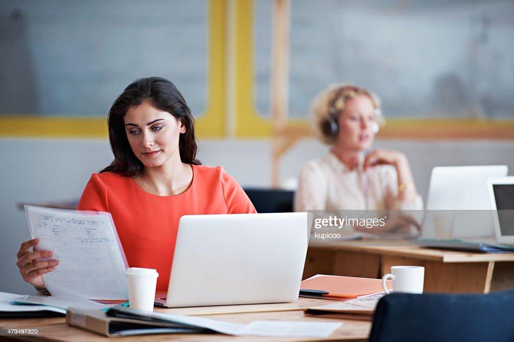 Cross-checking her analog and digital paperwork : Stock Photo