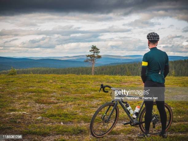 cross-country cyclist taking a break, looking at the distant hills in the finnish lapland - lange mouwen stockfoto's en -beelden