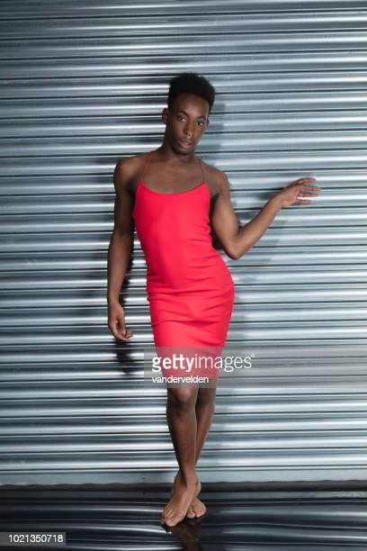 crossdressing man wearing a red dress - industrial door stock pictures, royalty-free photos & images
