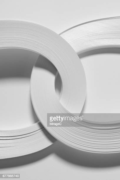 crossed interleaving paper rings - link chain part stock photos and pictures