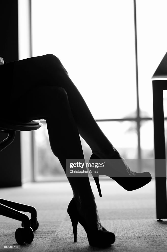 Crossed legs with high heels in the office : Stock Photo