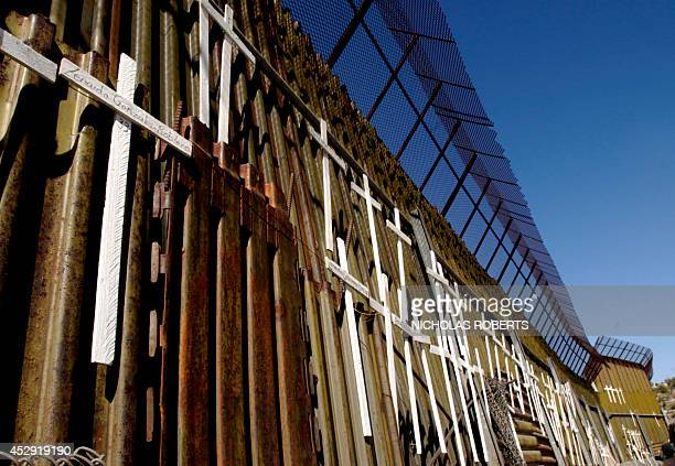 Crosses commemorating migrants who have died crossing the USMexico border hang on the Mexican side of the border fence separating the US and Mexico...