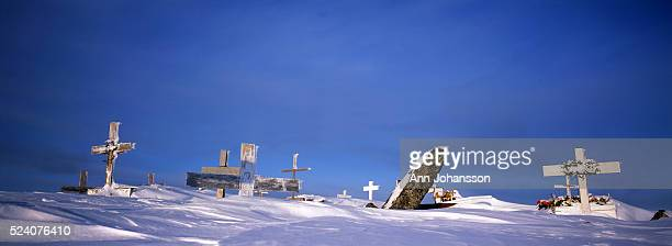 Crosses marking graves stick up through snow at the graveyard outside the village of Gambell on St. Lawrence Island, in Alaska.