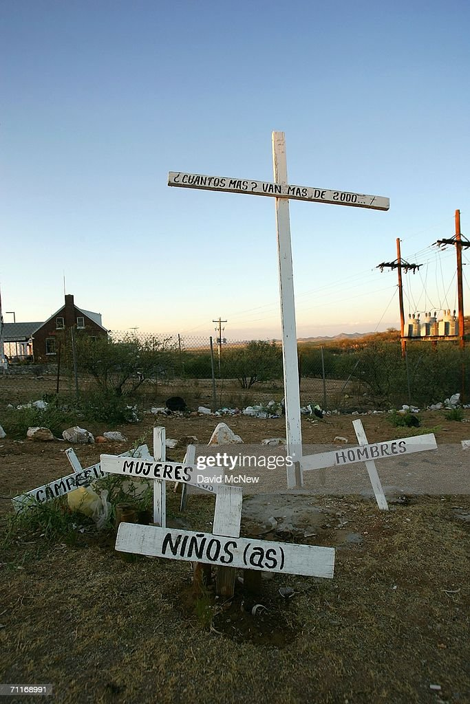 Crosses on the Mexican side of the U.S.-Mexico border memorialize illegal immigrants who died crossing the border, with the question 'How many more?' and the reply 'More than 2,000' dead written on them on June 7, 2006 in Sasabe, Mexico, 60 miles north of Altar, Mexico. Many thousands of one gallon water bottles litter the desert north of the border as immigrants drop them during their trek. More illegal immigrants pass through Altar where immigrant smuggling is the primary industry, than any other town. Available services include 'coyotes' or guides, transportation over 60 miles or more of dirt road in vans carrying as many as 25 people, about 150 'hospedajes' or guest houses, provisions, a free mobile clinic catering mostly to people who were hurt trying to cross the border, and groups who warn immigrants on the dangers of the trek and help those in need. From here, most immigrants are guided through Sasabe, where nightly robberies have become an industry and rape is common, then across the US-Mexico border to walk for about 45 miles through the desert before being picked up by smuggler vehicles. It is during the walk that most of the 473 deaths of 2005 occurred, mostly from exposure to extreme heat and fatigue.