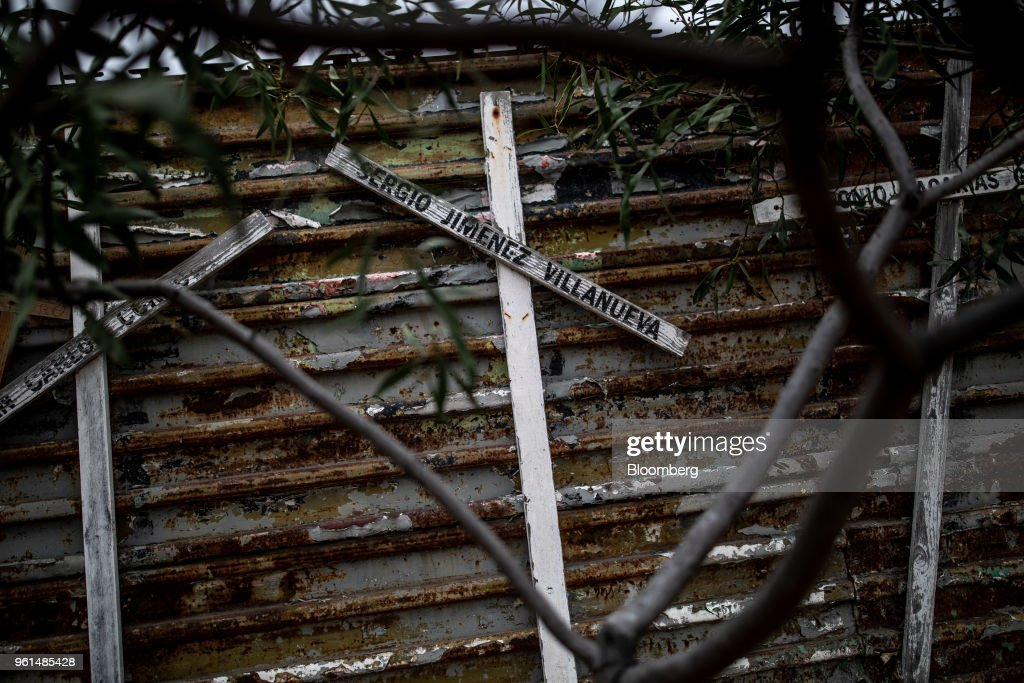 Crosses with the names of people killed trying to cross into the United States hang on a border fence in Tijuana, Mexico, on Monday, May 21, 2018. 'We won't care about threats of a wall,' National Regeneration Movement Presidential candidate Andres Manuel Lopez Obrador announced assuring another rally crowd in Zacatecas, one of the states that sends the most migrants to the U.S., that with him in power, they'll achieve equal footing with their neighbors to the north. Photographer: Alejandro Cegarra/Bloomberg via Getty Images