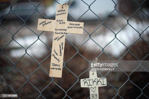 Crosses with the names of the victims of a mass shooting are pictured at a King Soopers grocery store in Boulder, Colorado hang from the perimeter...