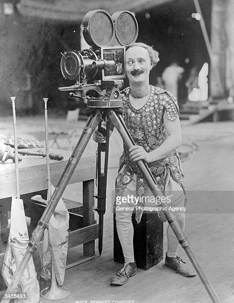 Crosseyed American comedian and actor Ben Turpin in costume from an unidentified Mack Sennett comedy operates a movie camera mid 1920s