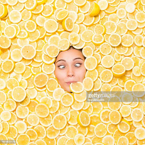 cross-eyed woman surrounded with lemon slice - acid stock photos and pictures