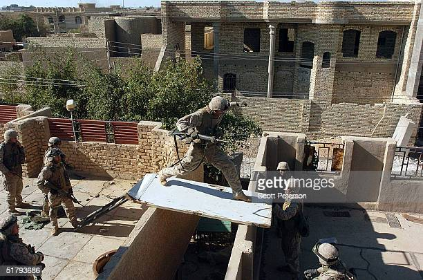 Crossing from roof to roof US Marines of the 1st Light Armored Reconnaissance company as part of 1st Battalion 3rd Marines clear and search houses...