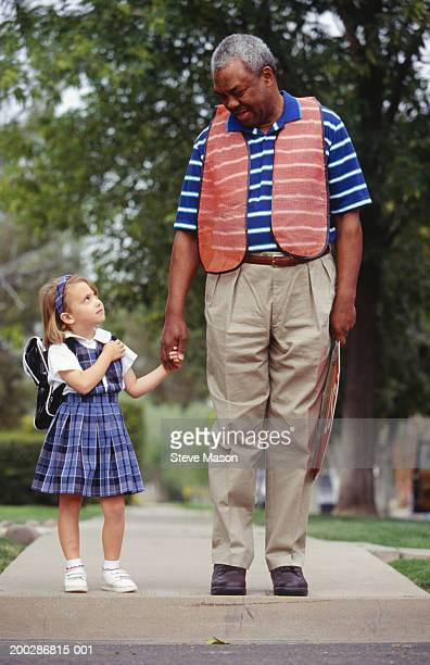 Crossing guard and girl (4-5) standing on kerb, looking at each other