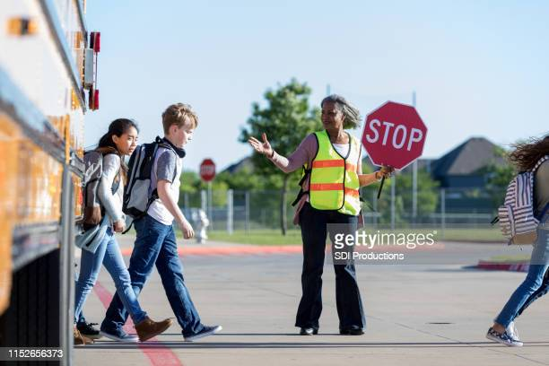 crossing guard protects students crossing the street - guarding stock pictures, royalty-free photos & images
