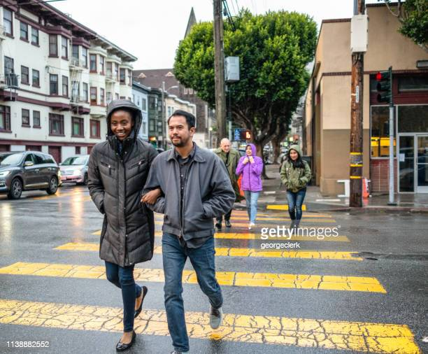 crossing in the rain - mission district stock photos and pictures