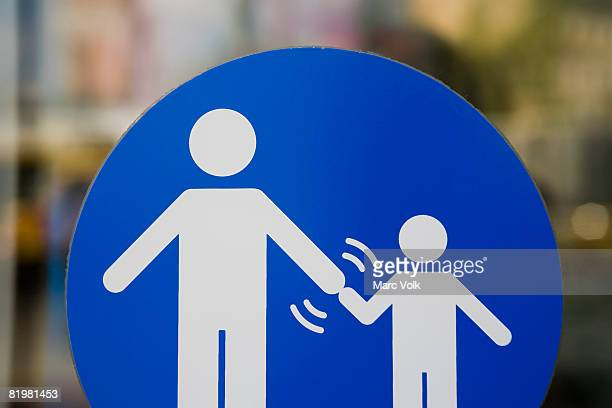 A crossing sign that indicates adults must hold a child?s hand