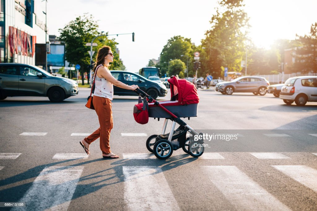 Crossing the boulevard with baby in prams with heavy traffic in rush hour : Stock Photo