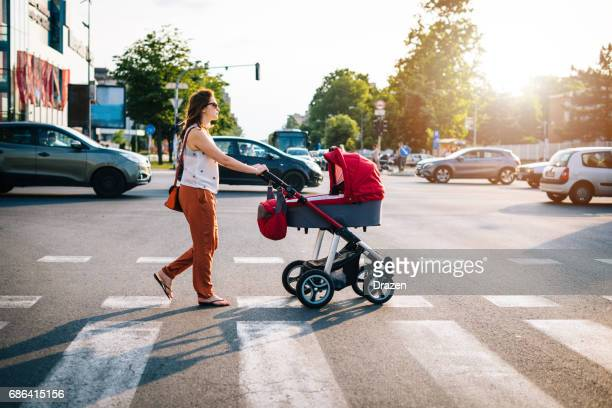 Crossing the boulevard with baby in prams with heavy traffic in rush hour