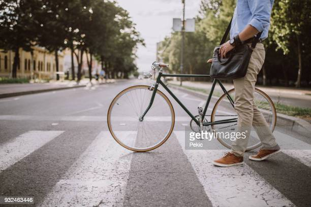 crossing the street with the bicycle - vita cittadina foto e immagini stock