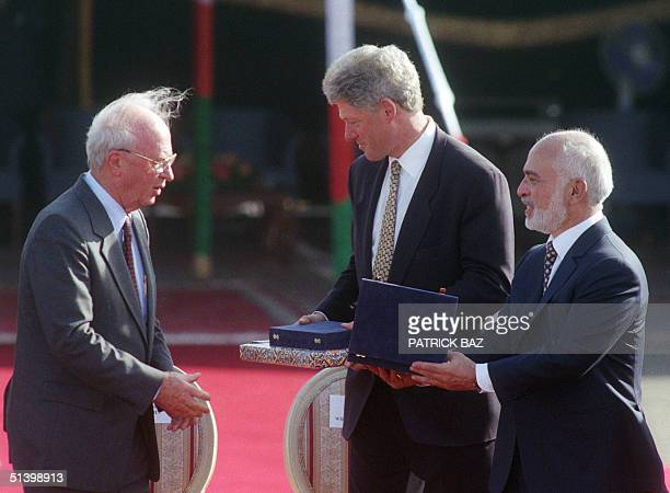 Jordanian King Hussein and Israeli Prime Minister Yitzhak Rabin exchange presents while US President Bill Clinton who already received his gift looks...