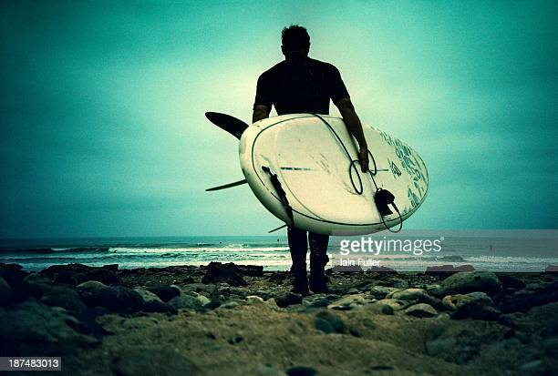 CONTENT] Crossprocessed Lomo shot of a man carrying a stand up paddle board into the sea