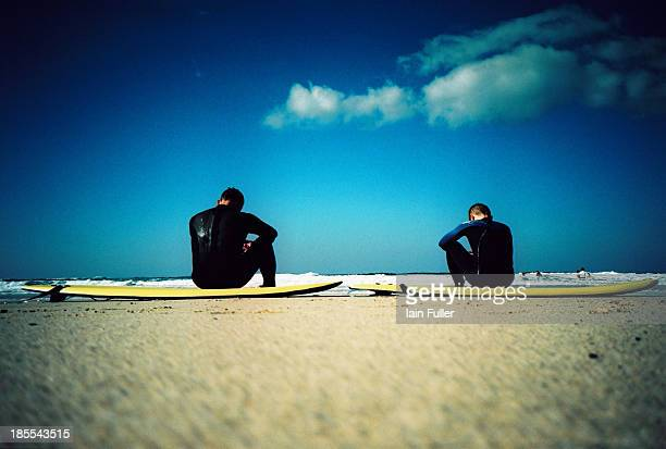 Cross-processed Lomo shot of two guys taking a break on the beach during a surfing lesson in Cornwall.