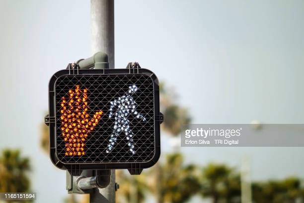 Crosswalk street sign with stop and walk lights turned on