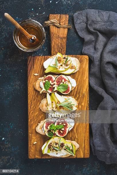 Crostini with pear, ricotta cheese, honey, figs, nuts and herbs on rustic board