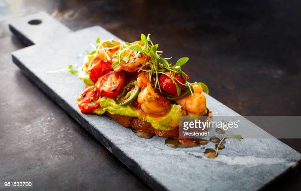 crostini with shrimps and tomatoes, roasted bread, herbs, avocado cream, sweet chili sauce, jalapenos, cress - appetiser stock photos and pictures