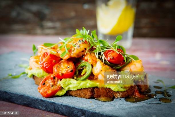 crostini with shrimps and tomatoes, roasted bread, herbs, avocado cream, sweet chili sauce, jalapenos, cress - avocado toast stockfoto's en -beelden