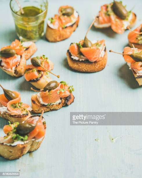 Crostini with smocked salmon, pesto sauce, watercress and capers over light blue background
