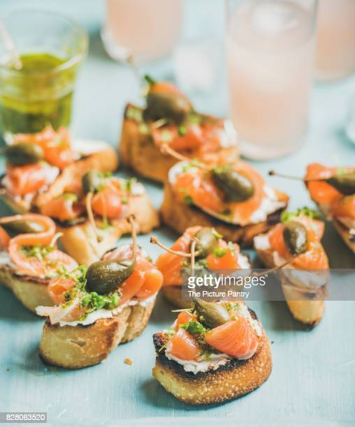 Crostini with smoked salmon, pesto sauce, watercress and capers and pink grapefruit cocktails over light blue background