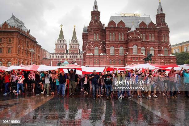 Crotian football fans shelter from a downpour under a giant Croatian flag near Red Square ahead of tonight's World Cup semifinal game between England...