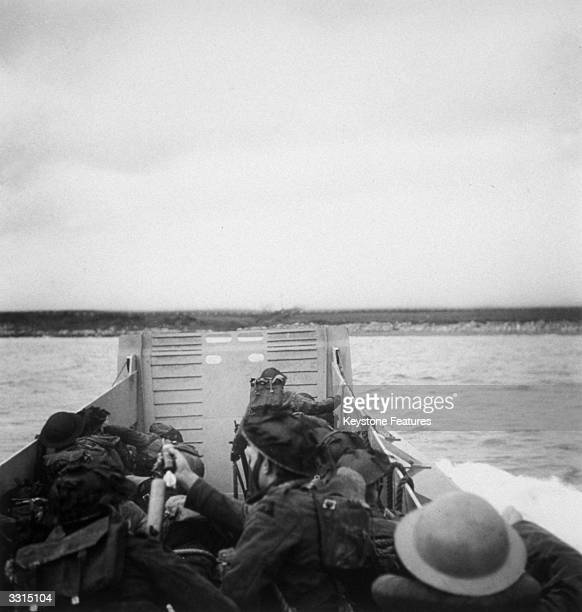 Crouched low in the landing craft with weapons at the ready these soldiers speed through rough seas to the 'attack' during invasion rehearsals