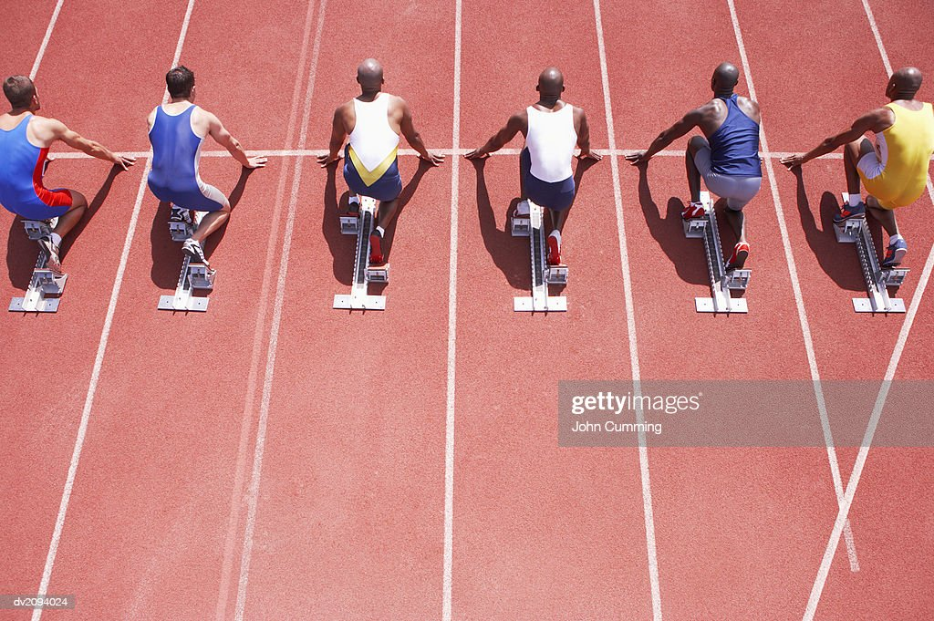 Crouching Athletes Lined Up on Starting Blocks on a Running Track : Stock Photo