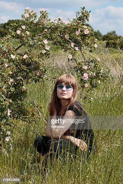 Hockend Lettische im Freien Mädchen mit Hund rose bush in Wiese