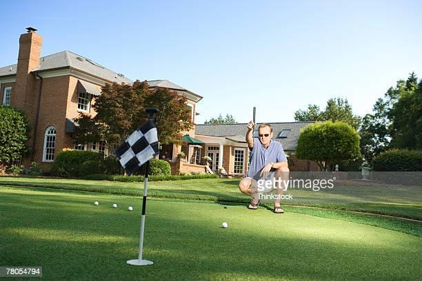 Crouching man planning next putt on backyard green