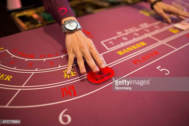 A croupier arranges a player's button on a baccarat table inside the Broadway Macau casino developed by Galaxy Entertainment Group Ltd in Macau China...