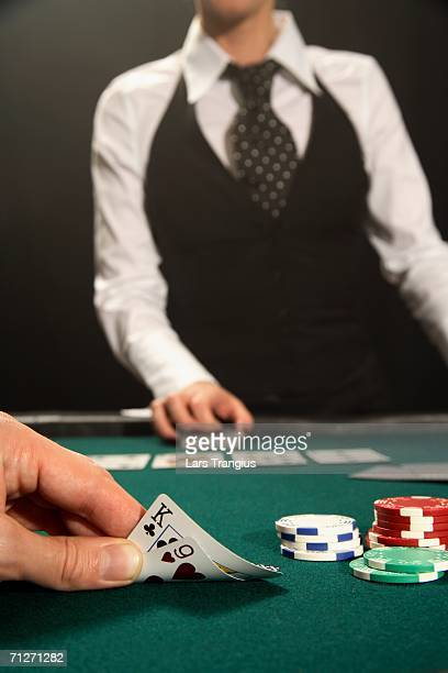 a croupier by a poker game. - gambling table stock pictures, royalty-free photos & images