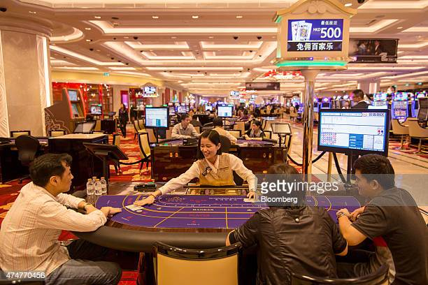 A croupier deals cards to people roleplaying as customers at a baccarat table in the Galaxy Macau Phase 2 casino developed by Galaxy Entertainment...