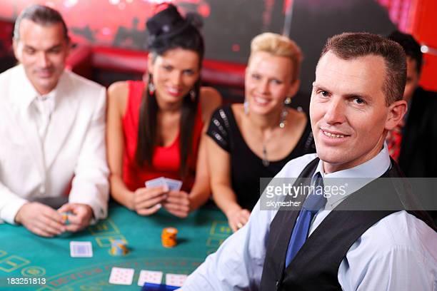 Croupier looking at camera, behind his gamblers playing Blackjac
