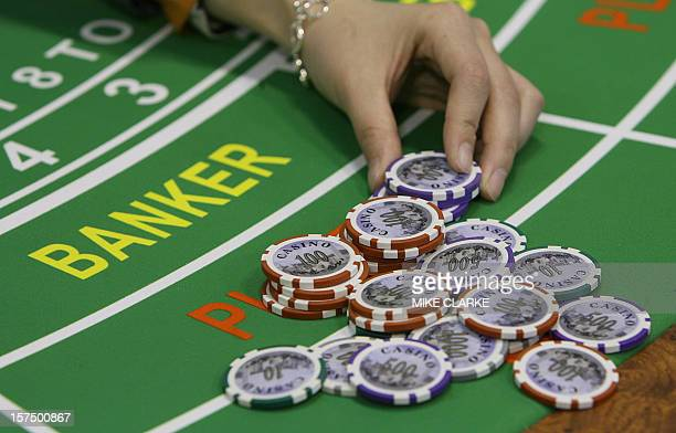 A croupier poses with gaming chips at a gaming booth in Macau 14 March 2007 The 6th International Gaming and Entertainment Expo was created to cope...