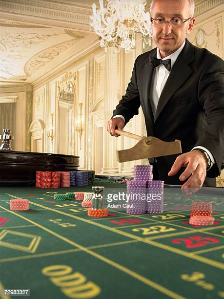 croupier raking chips at roulette table in casino - gambling table stock pictures, royalty-free photos & images