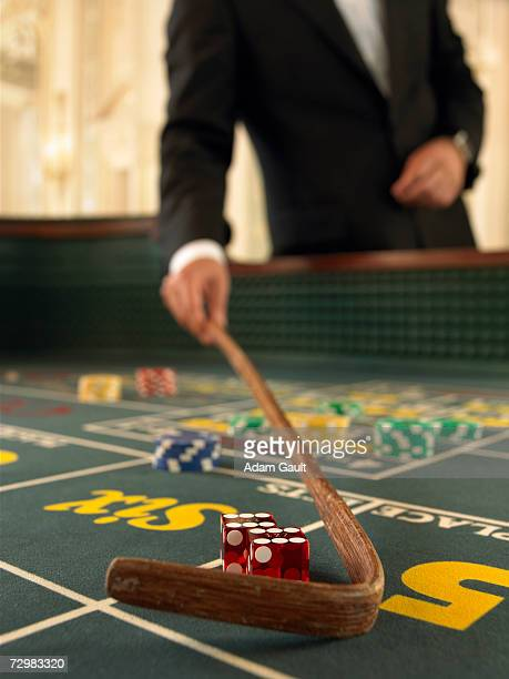 Croupier raking dice on craps table in casino