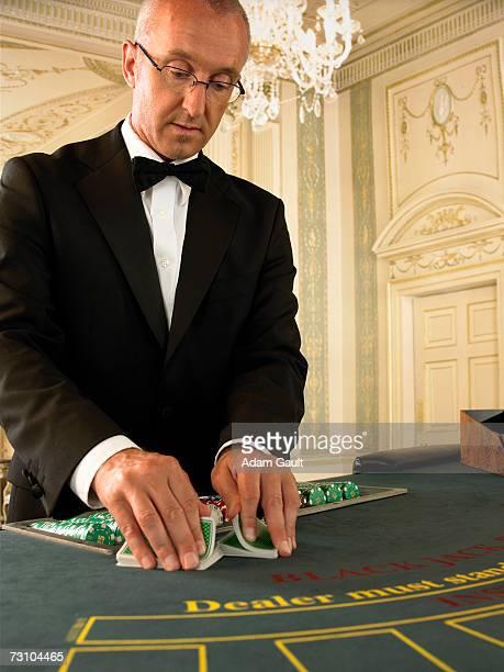 Croupier shuffling cards at blackjack table