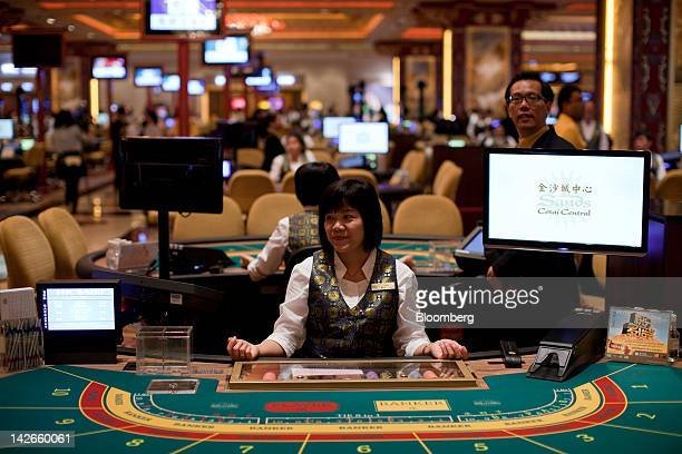 A croupier sits at her baccarat table in the Sands Cotai Central casino resort on its opening day in Macau China on Wednesday April 11 2012 Las Vegas...