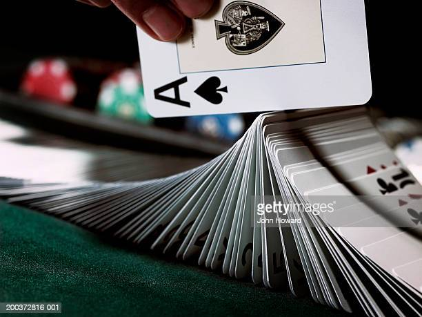 croupier turning pack of cards on gaming table with ace, close-up - shuffling stock photos and pictures