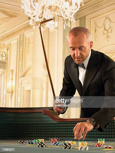 Croupier with rake at craps table in casino