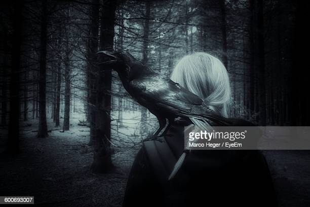 Crow Perching On Woman Shoulder In Forest