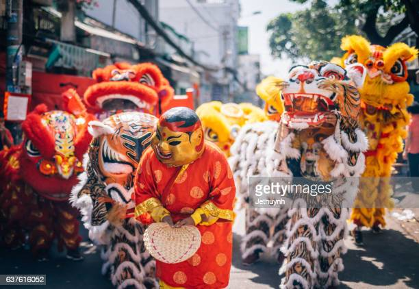 crowd and lion dancers in the celebration of the chinese new year in street at cho lon, ho chi minh city - chinese new year stock pictures, royalty-free photos & images